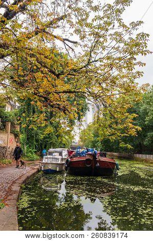 London, England - August 9, 2018: Man Walking His Dog Along Islington Canal In Angel, London.