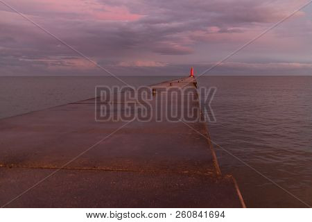A Lighthouse Pier On Lake Michigan At Dusk With Purple Clouds Reflected In The Water.  Sheboygan, Wi