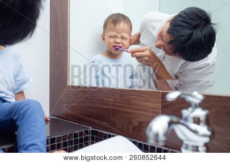 Asian Father Teaching Kid Teeth Brushing, Cute Little 18 Months / 1 Year Old Toddler Boy Child Brush