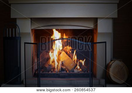 A Warm Fire In The Stone Fireplace On A Cold Night. Warm Cozy Fireplace With Real Wood Burning In It