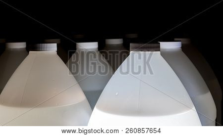 White Plastic Containers Full Of Fluid With Lids And Black Background
