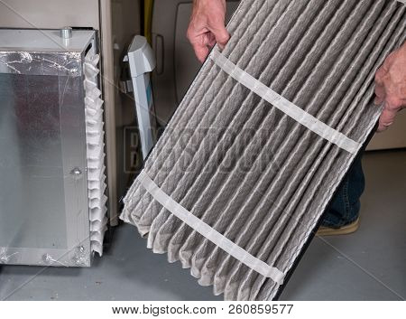 Senior Caucasian Man Examining A Folded Dirty Air Filter In The Hvac Furnace System In Basement Of H