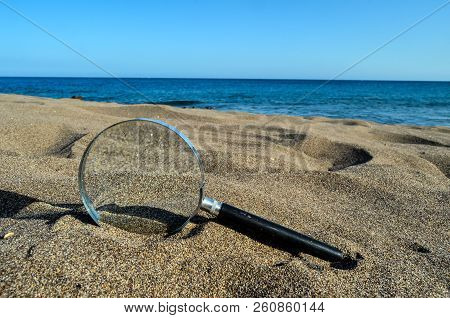Photo Picture Of A Loupe Magnify Glass On The Sand Beach