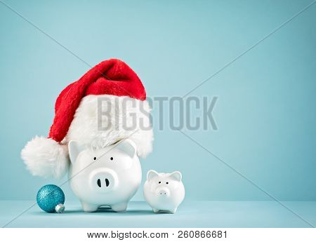 Piggy Bank Wearing Santa Hat - Family Saving Money For Christmas Concept