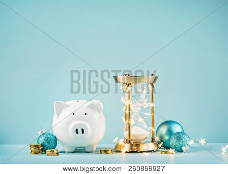 Piggy Bank And Rustic Hourglass Wrapped In Lights On A Blue Background. Countdown To Save For The Ch