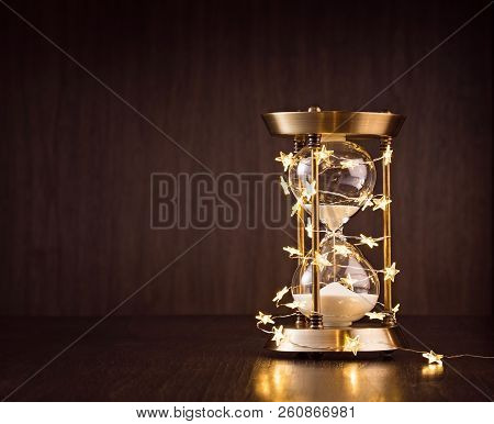 Christmas Or New Years Countdown. Rustic Hourglass Wrapped In Lights With Sand Trickling Through On