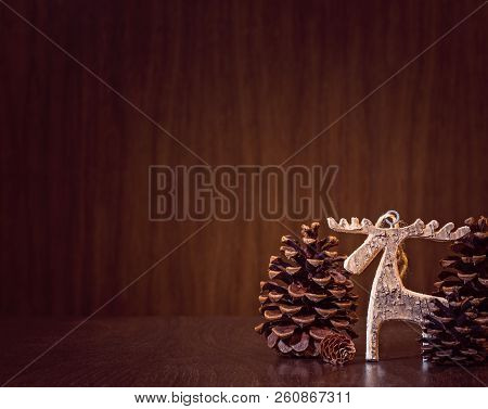 Simple, Natural Christmas Background With A Rustic Wooden Moose Ornament And Pinecone Trees On Dark