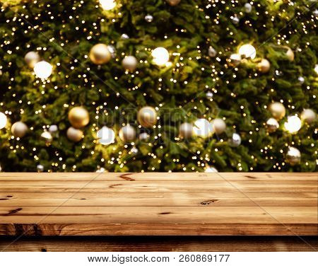 Christmas And New Year Background With Empty Wooden Deck Table Over Blurred Christmas Tree At Night.