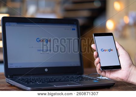 Chiang Mai, Thailand - Sep. 08,2018: Man Holding Huawei And Using Laptop With Google Search On Scree