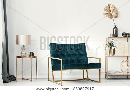 Dark Green Sofa With Golden Frame By A White Wall With Molding In An Elegant Living Room Interior Wi