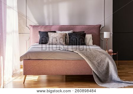 Grey Blanket And Black Pillows On Pink Bed In Hotel Bedroom Interior With Lamp On Table. Real Photo