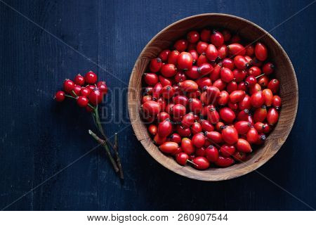 Freshly picked rose hips. Wooden bowl of rose hip or rosehip, commonly known as the dog rose (Rosa canina).
