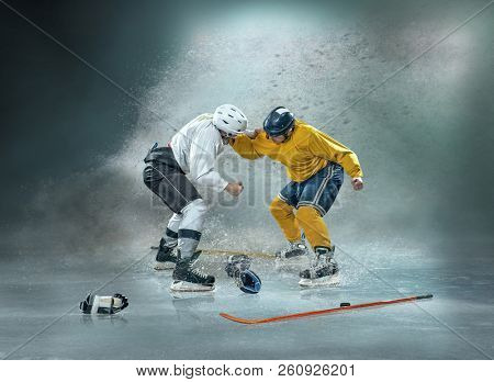 Caucassian ice hockey Players in dynamic boxing action in a professional sport game play in hockey around splash drops.