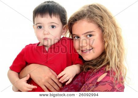 Beautiful 12 year old girl holding toddler boy. Shot in studion over white.