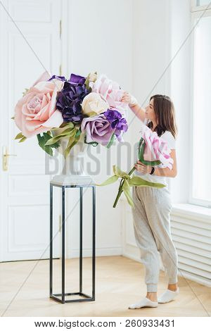 Indoor Shot Of Female Florist Holds Rose, Creats Beautiful Bouquet, Decorates Room, Owns Flower Shop