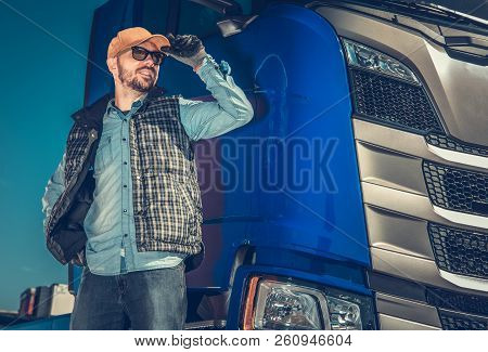 Semi Truck Driver And Hit Modern Vehicle. Happy Caucasian Trucker In His 30s. Transportation Industr