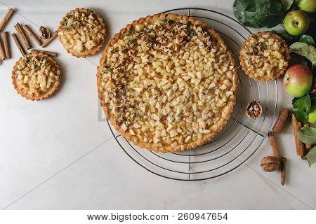 Homemade Sweet Apple Shortbread Tart On Cooling Rack And Tartlets With Cinnamon Sticks, Walnuts, App