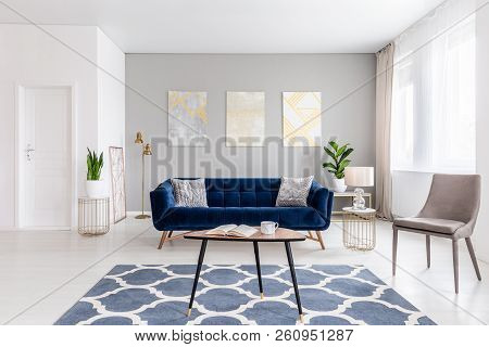 Open Space Living Room Interior With Modern Furniture Of A Navy Blue Settee, A Beige Armchair, A Cof