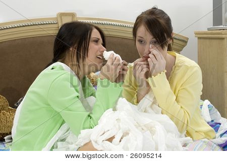 Two teen girls crying into a huge pile of toliet tissue.