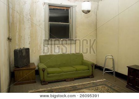 Impoverished home interior at night. Bare window, cracks in wall, old wooden floor and furniture.