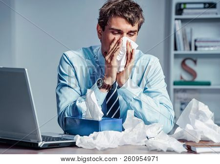 Sick Worker Blow His Nose In Paper Tissues. Photo Of Young Man Working In The Office. Business Conce