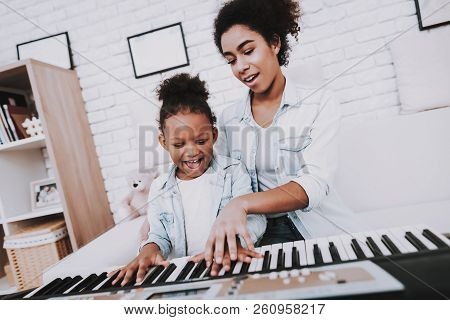 Mother With Daughter Play On Piano. Mother Help Girl With Piano. Positive Emotion. Smile Girl And Sm