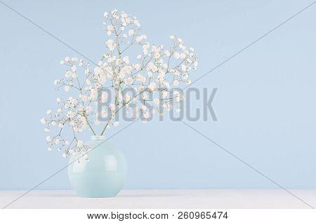 Spring Bouquet Of White Small Fluffy Flowers In Blue Smooth Circle Ceramic Vase On Soft White Wood T