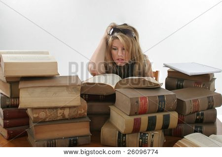 Stressed out teen girl surrounded by old law book.  Book 70 years old.