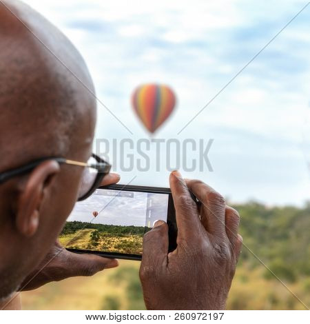 A man taking photos with a cell phone whilst on a balloon ride in the Masai Mara. Selective focus on the image on the phone screen.