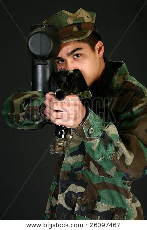 Attractive Filipino 16 year old boy in camo gear aiming paintball rifle.