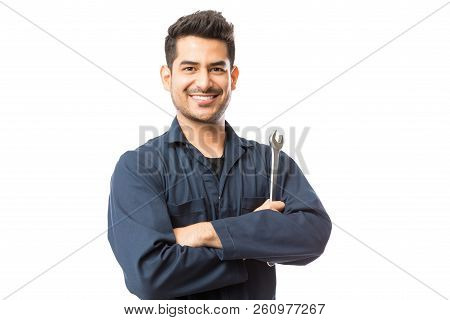 Smiling Auto Mechanic With Wrench Standing Hands Folded On White Background