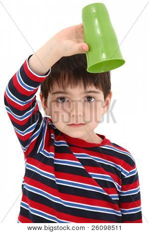 Child holding empty cup upside down with disappointed expression.