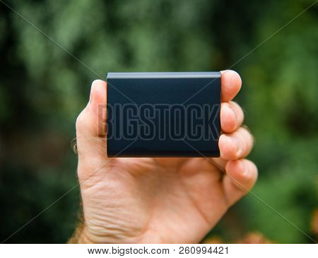 Man hand holding Portable SSD 2 tb external hard drive disk with high read and write speed against green background unboxing testing poster