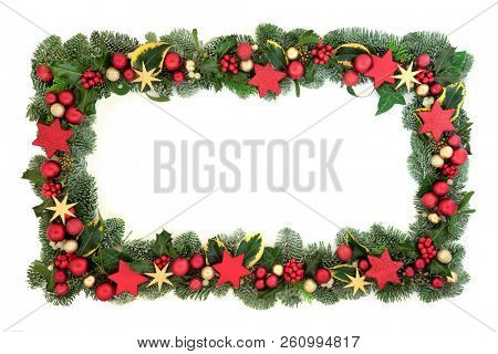 Decorative Christmas background border with red and gold star and ball bauble decorations with winter flora of holly, ivy, mistletoe and spruce fir. Festive theme.