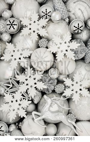 Christmas background with white and silver baubles with star, snowflake, reindeer, snowflake, balls and pine cone decorations. Traditional christmas greeting card for the holiday season. Top view.