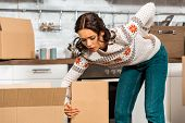 young woman having pain in back while carrying cardboard boxes during relocation at new home poster