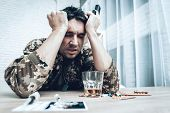 A Man In Camouflage At Home With Shotgun. Depression After War Concept. Sad Homecoming. Returning From Army. Posttraumatic Disorder. Painful Memories. Photo From War. Glass Of Whiskey. poster