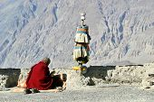Buddhist monk reading a religious text with Himalaya mountains background poster