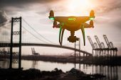 Silhouette of Unmanned Aircraft System (UAV) Quadcopter Drone In The Air Over Shipping Port. poster
