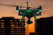 Silhouette of Unmanned Aircraft System (UAV) Quadcopter Drone In The Air Over Buildings Under Construction. poster