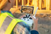 Female Unmanned Aircraft System (UAV) Quadcopter Drone Pilot with Controller Inspecting New House Framing. poster