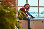 Young beautiful student girl sitting with laptop on window sill in student dormitory. poster