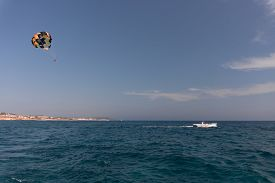 Parasailing. The Man Is Flying With A Yellow Parachute. Close-up.