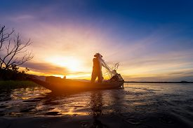 Silhouette Of Fishermen Using Nets To Catch Fish At The Lake In Thailand Morning Light.