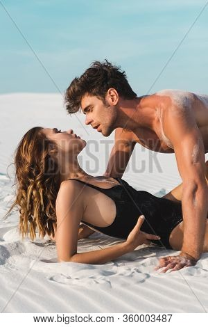 Sexy Young Man Looking At Girlfriend On Sandy Beach