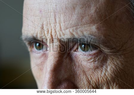 Eyes Of A Man Close-up. A Mature Man Frowns Aside.
