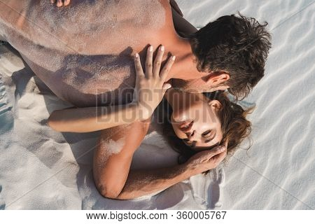 Top View Of Sexy Young Man Kissing Girlfriend On Sandy Beach