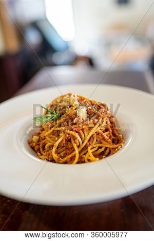 Spaghetti Bolognese Served On A White Plate In A Restaurant