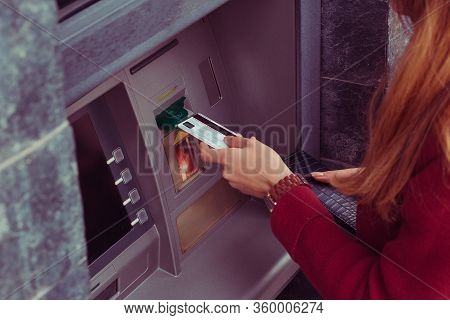 Close Up  Cropped Image Of Hand Pulling In Debit Card At An Atm. Hand Of Woman Uses Credit Card To W