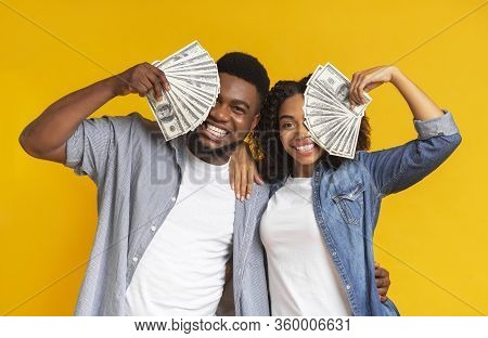 Lucky Black Man And Woman Holding Lots Of Dollar Cash, Covering Faces With Money And Cheerfully Smil